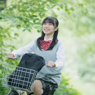 新緑の中で自転車に乗る女子学生の写真素材 [FYI02959222]