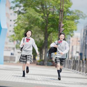 通学路を走る2人の女子学生の写真素材 [FYI02959228]