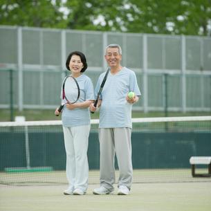 テニスラケットを持ち微笑むシニア夫婦の写真素材 [FYI02959247]