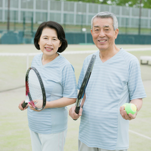 テニスラケットを持ち微笑むシニア夫婦の写真素材 [FYI02959248]