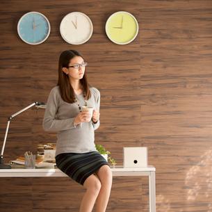 コーヒーカップを持ち机に寄りかかるビジネスウーマンの写真素材 [FYI02959299]