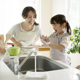 キッチンで手を洗う女の子と微笑む母親の写真素材 [FYI02959303]