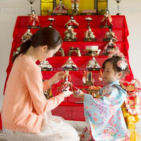 雛人形の飾り付けをする親子の写真素材 [FYI02959305]