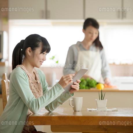リビングでタブレットPCを見る女の子の写真素材 [FYI02959307]