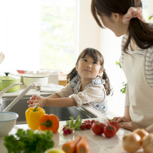 キッチンで野菜を洗う女の子と母親の写真素材 [FYI02959308]