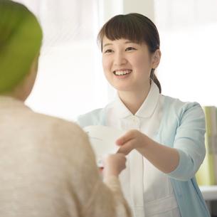 患者に薬を渡す女性職員の写真素材 [FYI02959338]