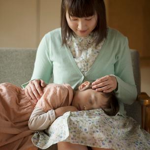 母親の膝の上で眠る女の子の写真素材 [FYI02959339]