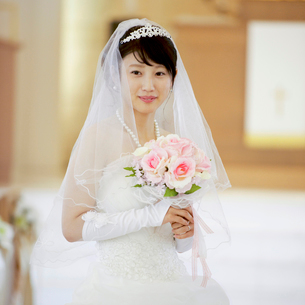 教会でブーケを持ち微笑む花嫁の写真素材 [FYI02959368]