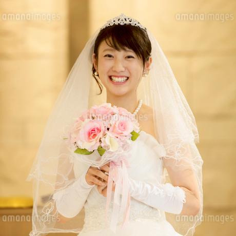 教会でブーケを持ち微笑む花嫁の写真素材 [FYI02959370]