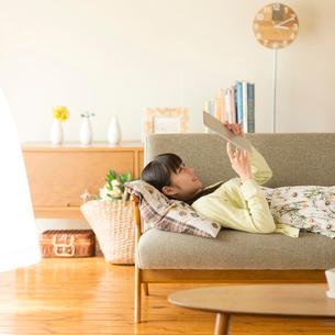 ソファーに寝転びタブレットPCを見る女性の写真素材 [FYI02959379]