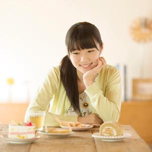 頬杖をつきお菓子を眺める女性の写真素材 [FYI02959384]