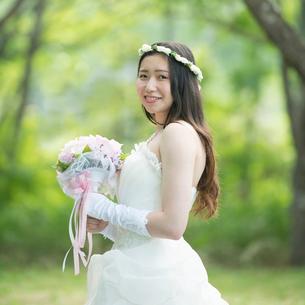 森林の中でブーケを持ち微笑む花嫁の写真素材 [FYI02959391]