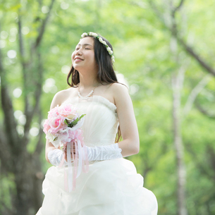 ブーケを持ち森林の中で目を閉じる花嫁の写真素材 [FYI02959394]
