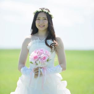 草原でブーケを持ち微笑む花嫁の写真素材 [FYI02959404]