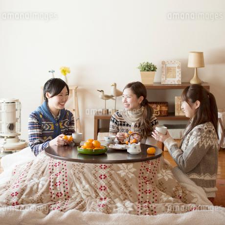 こたつで談笑をする3人の女性の写真素材 [FYI02959505]