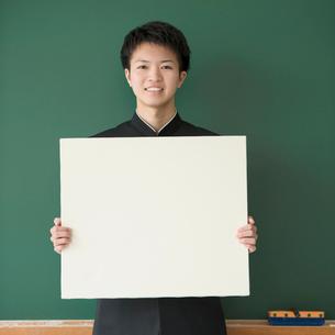 メッセージボードを持ち微笑む男子学生の写真素材 [FYI02959510]