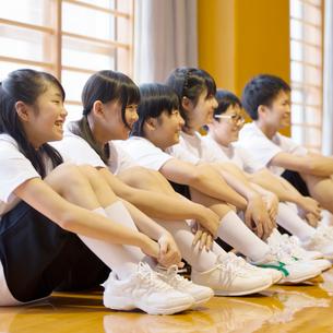 体育館で体育座りをする学生の写真素材 [FYI02959511]