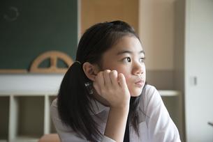 教室で外を見ている小学生の女の子の写真素材 [FYI02959546]