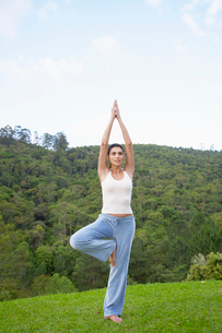 Young woman in tree pose on lawnの写真素材 [FYI02960285]
