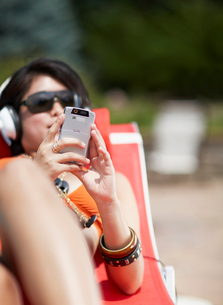 Mid-Adult Woman Listening to MP3 Player on Lounge Chairの写真素材 [FYI02960325]