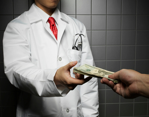 Doctor Receiving US Dollarsの写真素材 [FYI02960361]