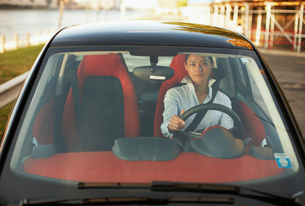 Front View of Mid-Adult Woman Driving Smart Carの写真素材 [FYI02960581]