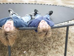Two Boys Lying on Trampolineの写真素材 [FYI02960604]