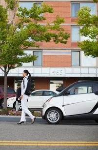Mid-Adult Woman Walking Near Smart Carの写真素材 [FYI02960666]