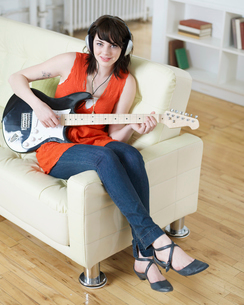 Young Woman Playing Electric Guitarの写真素材 [FYI02960719]