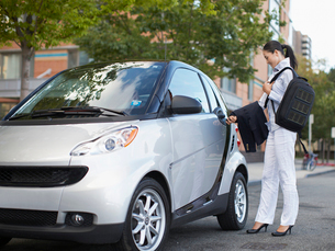 Mid-Adult Woman Getting Into Smart Carの写真素材 [FYI02960771]
