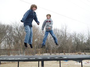 Two Children Jumping on Trampolineの写真素材 [FYI02960807]