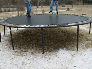 Low Section of Two Children Jumping on Trampolineの写真素材 [FYI02960873]