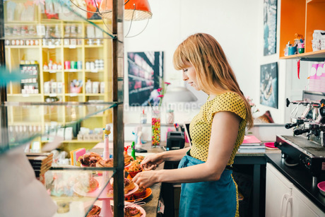 Side view of female barista with pastries at cafe counterの写真素材 [FYI02960875]