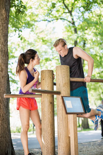 Woman motivating man in doing chin-ups on wooden bars at outdoor health clubの写真素材 [FYI02960985]