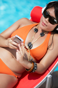 Mid-Adult Woman Listening to MP3 Player on Lounge Chairの写真素材 [FYI02961020]
