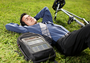 Young Businessman with Bicycle Lying on Grassの写真素材 [FYI02961053]