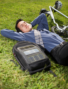 Young Businessman with Bicycle Lying on Grassの写真素材 [FYI02961081]
