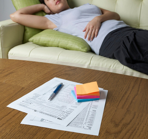 Tax Forms on Table, Woman Lying in Backgroundの写真素材 [FYI02961122]