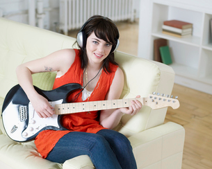 Young Woman Playing Electric Guitarの写真素材 [FYI02961166]