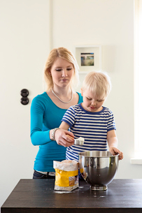 Finland, Helsinki, Kallio, Mother helping son add flour to mixer bowlの写真素材 [FYI02961304]