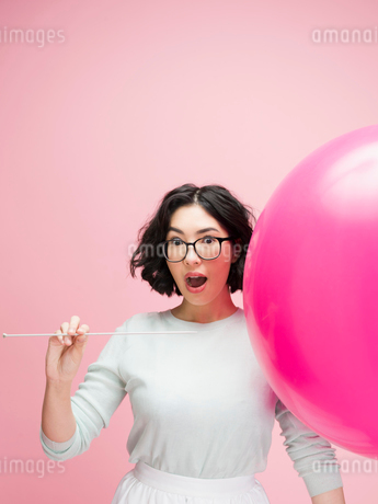 Portrait surprised young woman popping balloon against pink backgroundの写真素材 [FYI02961534]