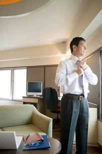 ホテルでネクタイを締めるビジネスマンの写真素材 [FYI02961677]
