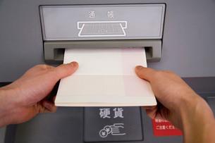 ATMに通帳を入れる人の写真素材 [FYI02961819]