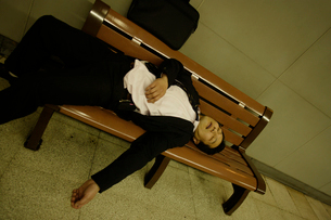 ベンチで居眠りをするビジネスマンの写真素材 [FYI02961911]