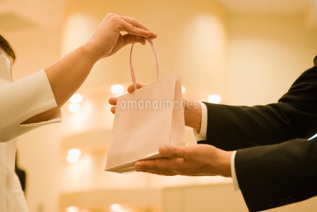 品物を手渡す店員の写真素材 [FYI02961997]