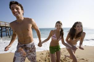 海岸で遊ぶ男性と女性二人の写真素材 [FYI02962019]