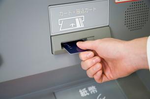 ATMにカードを入れる人の写真素材 [FYI02962023]