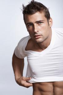 Mid adult man putting T-shirt onの写真素材 [FYI02962120]