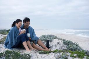 Mid adult couple drinking tea on beach,の写真素材 [FYI02962238]