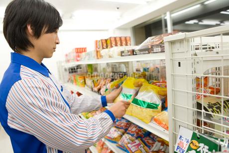 商品を整頓するコンビニの店員の写真素材 [FYI02963326]